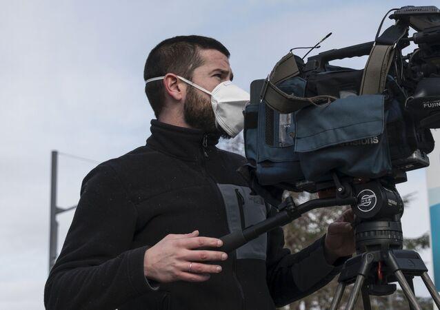 Un caméraman travaille avec un masque de protection.