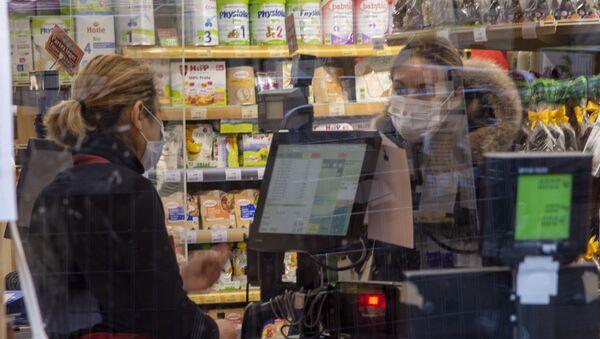 Une femme portant un masque dans un magazin à Paris - Sputnik France