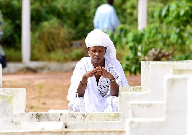 Une femme se recueille devant une tombe à Dakar, Sénégal.