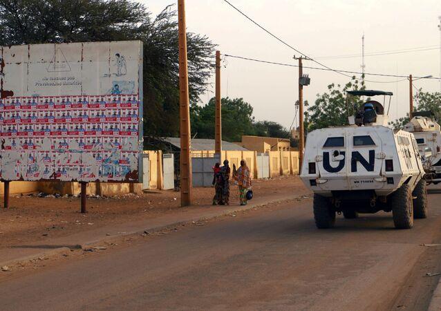 Un véhicule de la Minusma passe devant un placard d'affiches électorales au Mali.