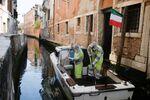 Dipendenti municipali in costumi protettivi disinfettano una barca a Venezia, Italia