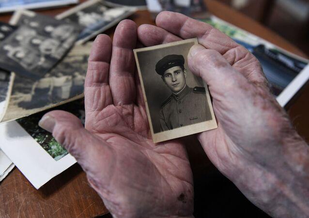 Le vétéran de la Grande guerre patriotique Alexeï Khavtourine regarde ses photos souvenirs