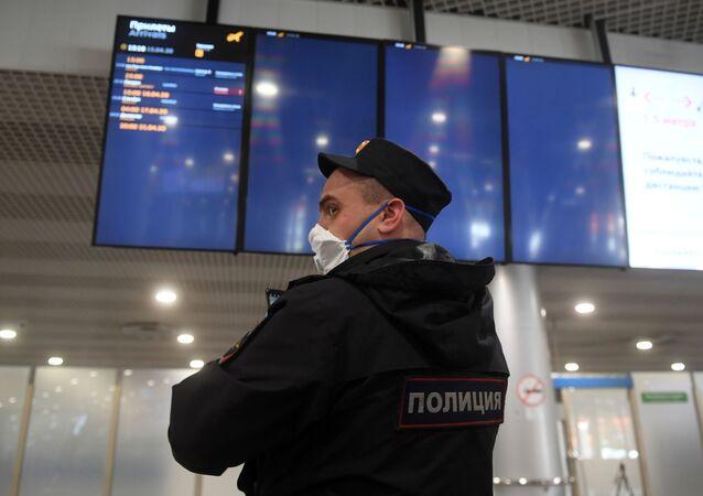 Un policier portant un masque à l'aéroport Cheremetievo
