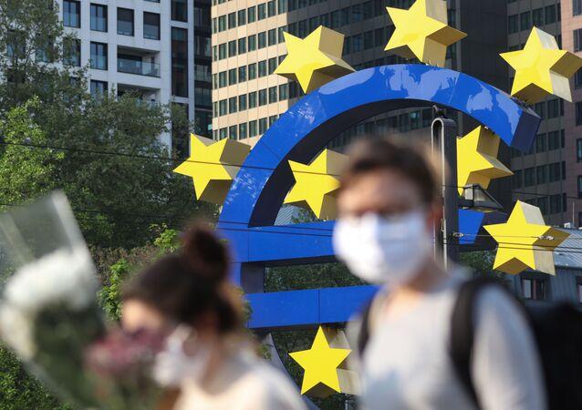 Passants en masques devant la Banque centrale européenne, Francfort (Allemagne), avril 2020