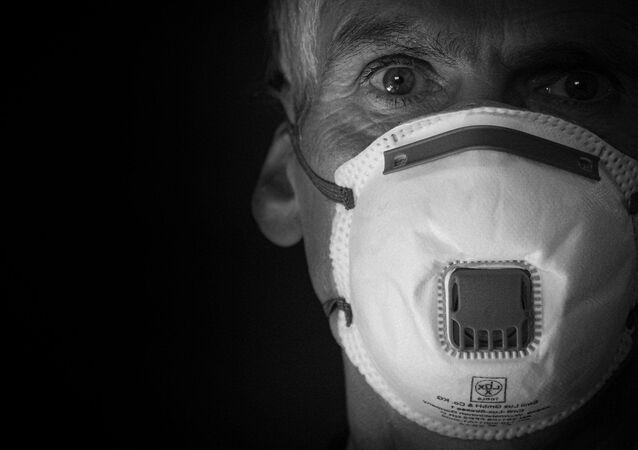 Une homme porte un masque de protection