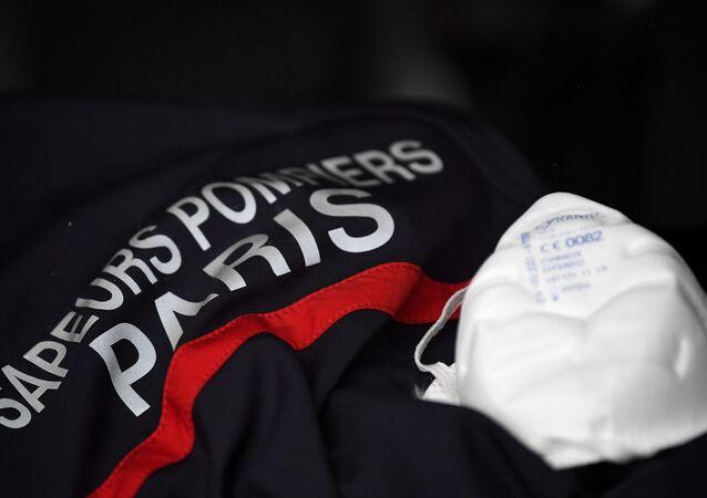 Un masque FFP2 et un uniforme de pompier de Paris