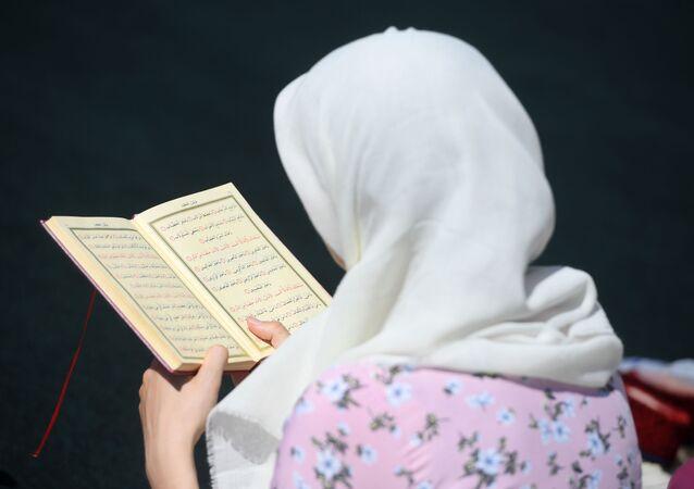 Une femme lisant le Coran, image d'illustration