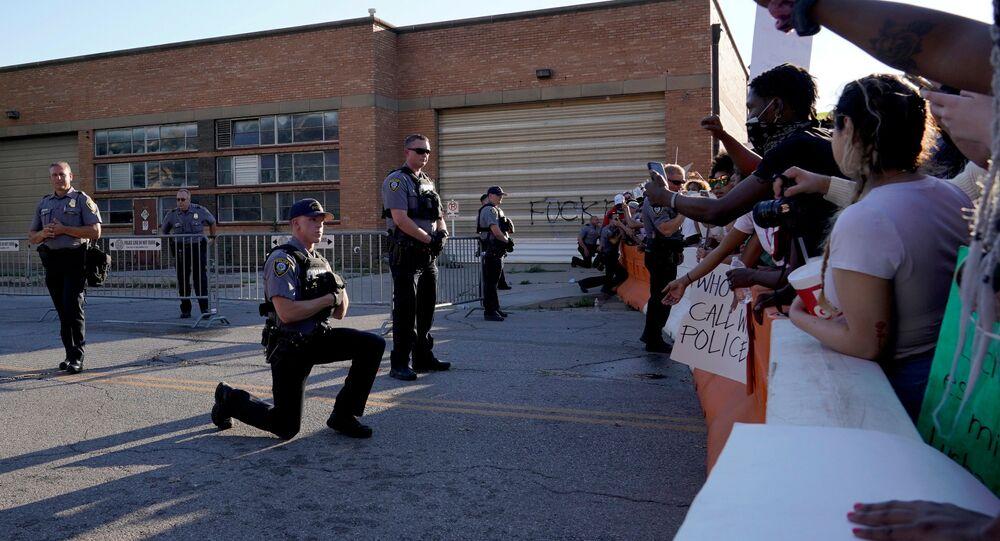 Un policier a mis un genou à terre devant des participants aux rassemblements aux États-Unis, le 31 mai 2020