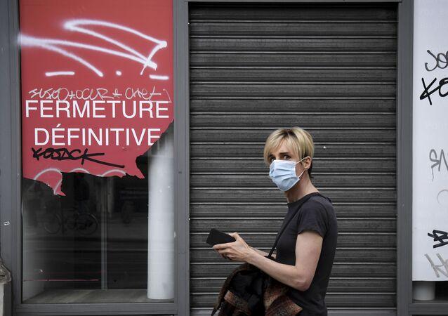 Personne portant un masque devant un magasin fermé à Paris, juin 2020