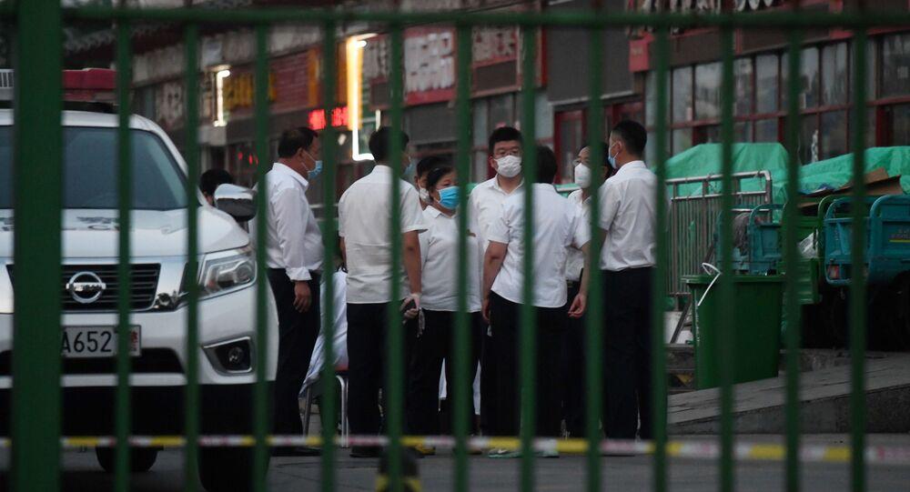 des autorités chinoises devant le marché de Xinfadi à Pékin, le 12 juin 2020
