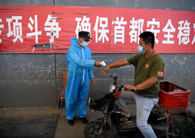 Le personnel de sécurité portant une combinaison de protection vérifie la température d'un homme sur une moto entrant sur le marché Xinfadi à Pékin, le 14 juin 2020