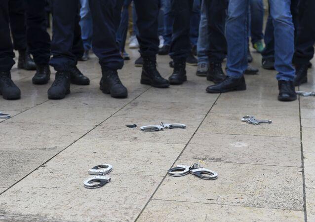 des policiers déposent leurs menottes, image d'illustration