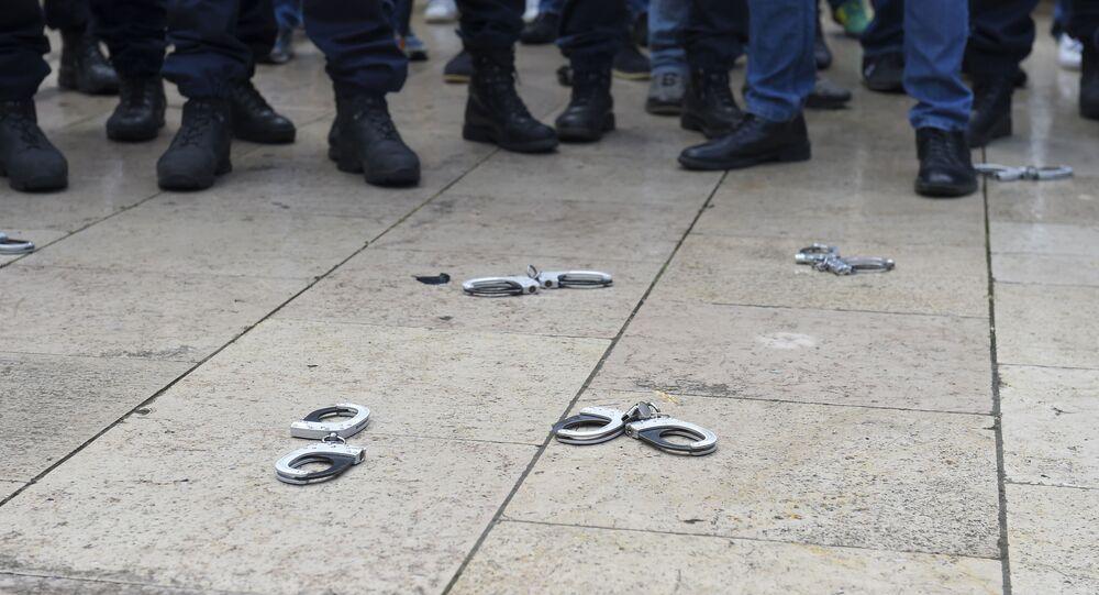 Des policiers français déposent symboliquement leurs menottes pour montrer leur colère. (Photo by NICOLAS TUCAT / AFP)