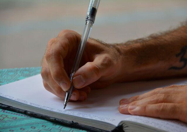 Une main avec un stylo (image d'illustration)