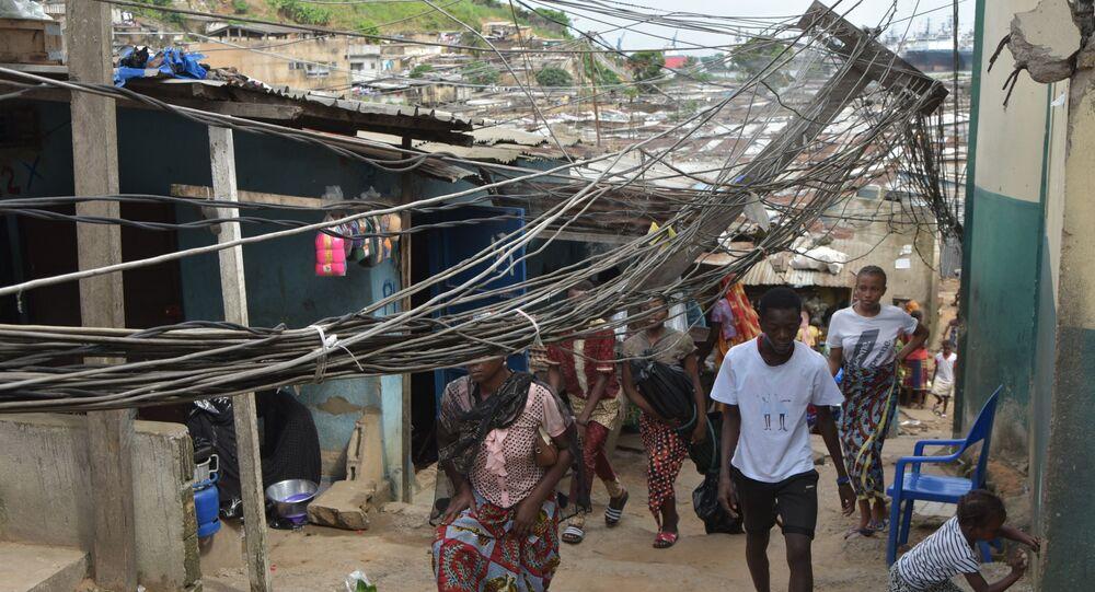 Des passants sous des fils électriques tombés d'un toit.