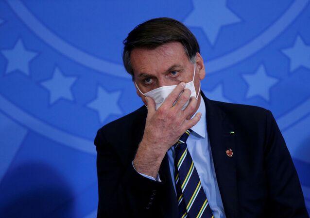 Le President Jair Bolsonaro ajuste un masque durant l'épidémie