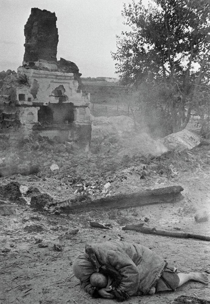 Une mère protège son enfant pendant un raid aérien contre le village de Krasnaïa Sloboda, dans la région de Briansk (1941)